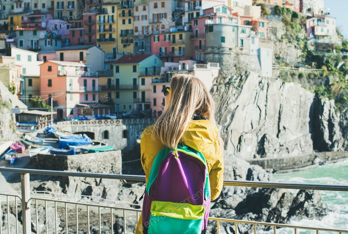 Young blond tourist woman in Riomaggiore, Cinque Terre, Italy