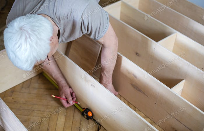 Mature man measuring wooden shelf with reel while  shelf unit