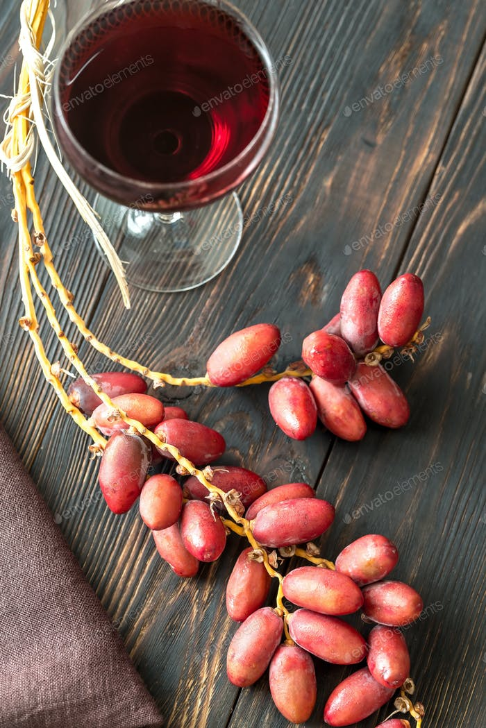 Glass of red wine with bunch of dates
