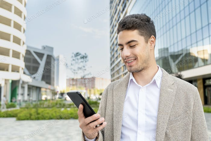 Young cheerful businessman in formalwear looking at screen of mobile phone