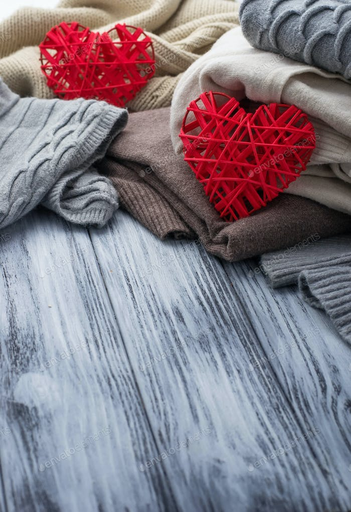 Warme gestrickte Pastellkleider und Herzen