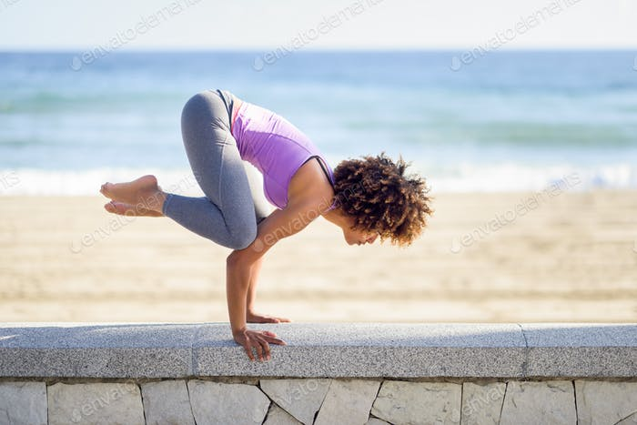Black woman, afro hairstyle, doing yoga in the beach