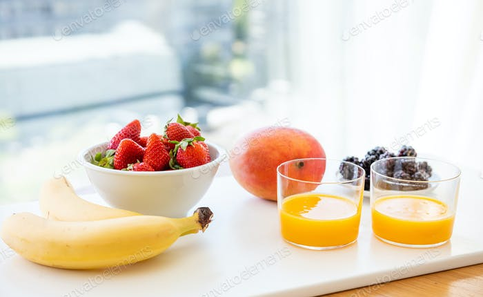 Fresh fruits and orange juice isolated on white. Healthy breakfast for two.