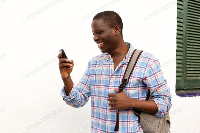 young african guy outside with bag and using mobile phone