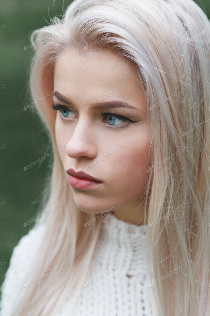 Portrait of a beautiful serious blonde girl in a white knitted sweater. Close-up profile