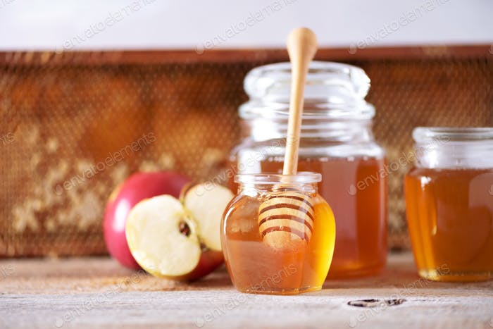 Apples with honey jar, honeycomb on grey background with copy space. Rosh hashanah jewish new year