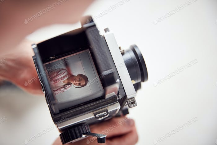 Photographer Looking Into Viewfinder Of Vintage Medium Format Camera On Photo Shoot