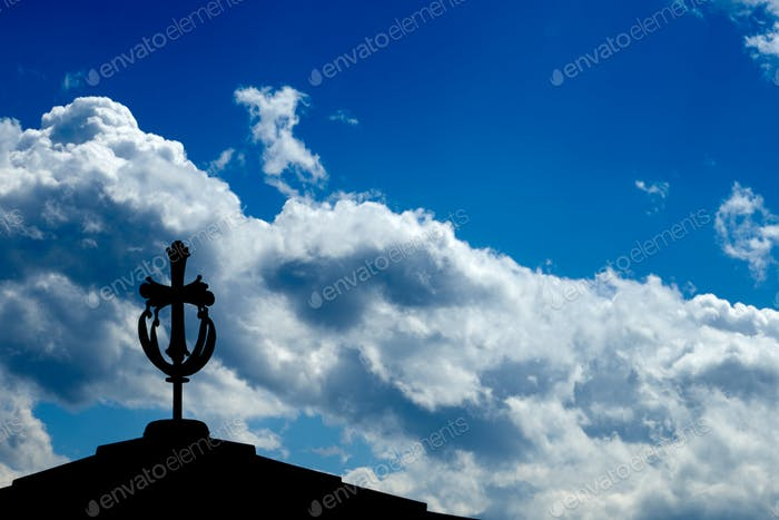 Cross on a monastery roof with a blue sky
