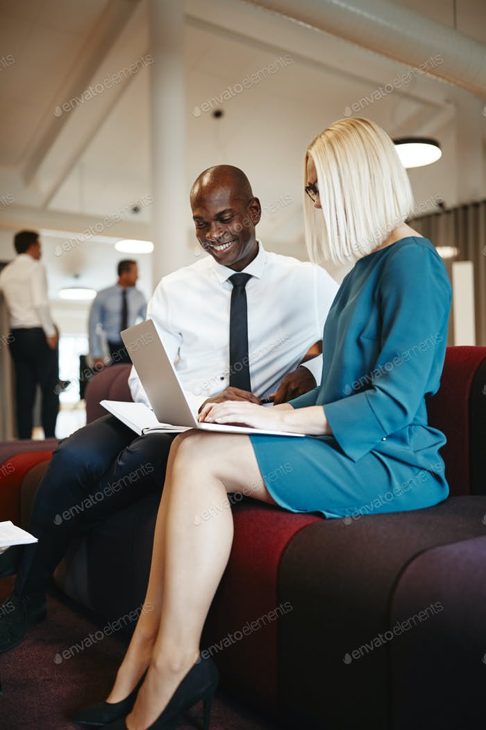 Smiling businesspeople sitting on an office sofa working online