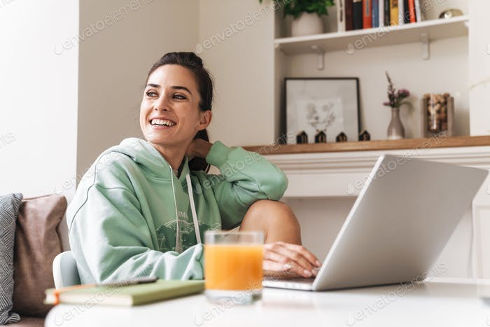 Cheerful beautiful brunette woman using laptop computer.