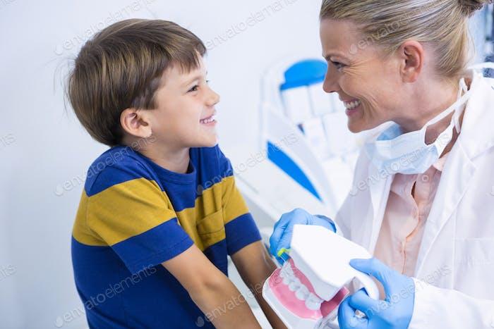 Glückliche Zahnarzt hält Zahnform beim Blick auf Junge
