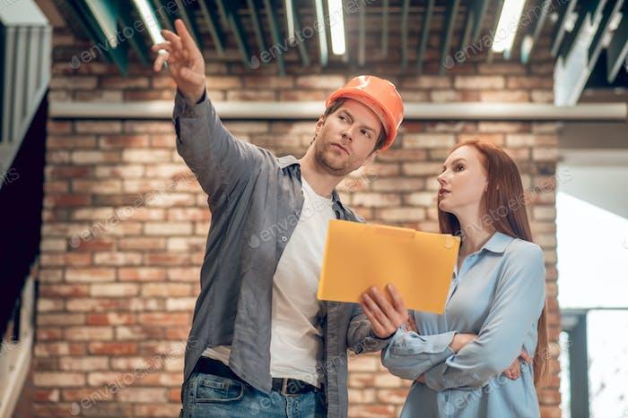 Man explaining showing construction plan to woman