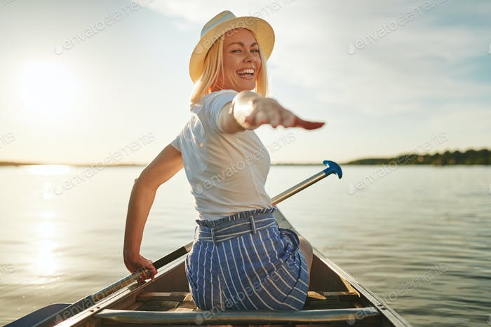 Smiling woman reaching out her hand while paddling a canoe
