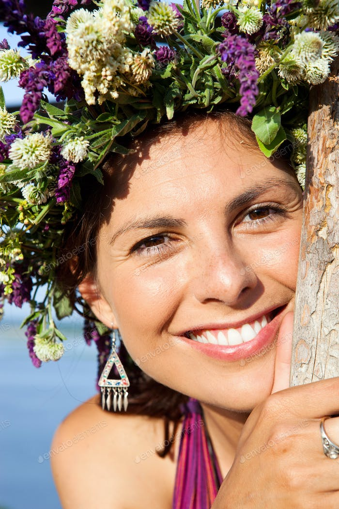 Portrait of gorgeous young woman wearing floral wreath