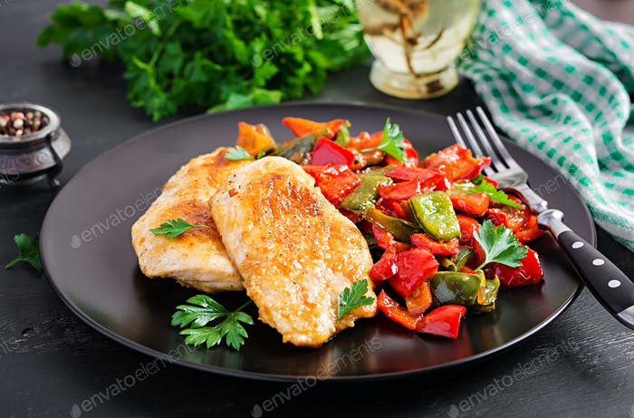 Grilled chicken fillets and sweet pepper on black plate.
