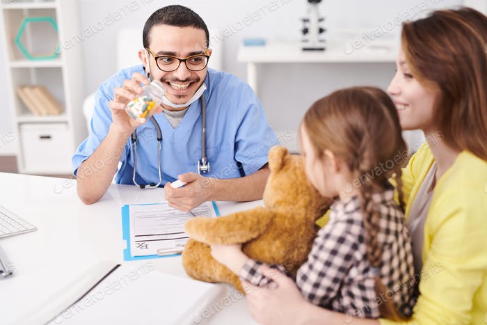 Friendly Pediatrician Working with Child in Clinic