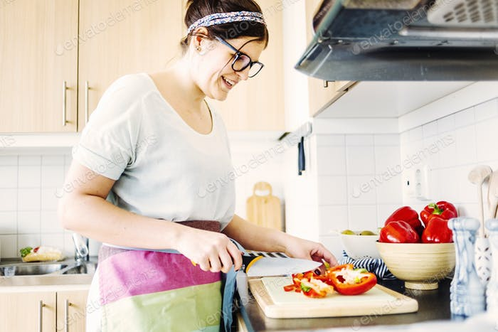 Smiling woman cutting red bell pepper at kitchen counter