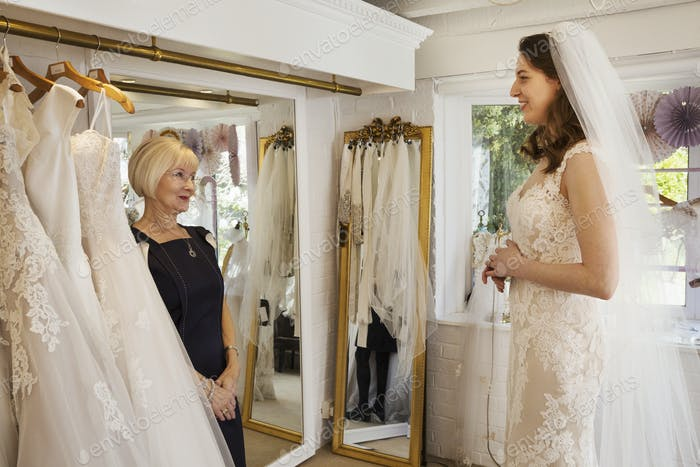 Eine Frau, eine Braut zu sein, versucht Kleider mit Hilfe eines Verkaufsassistenten, in einem Hochzeitskleid
