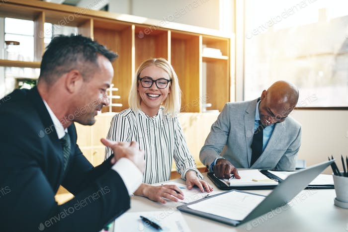 Diverse group of laughing businesspeople meeting together in an office