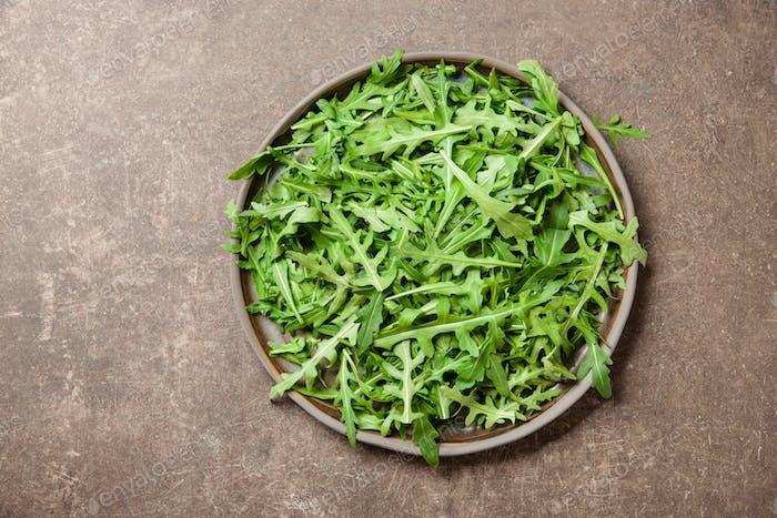 Fresh rucola leaves on ceramic plate