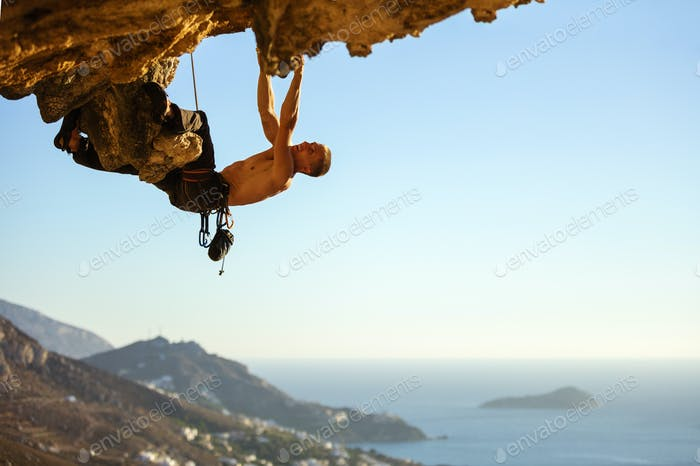Young man climbing on roof in cave, view of coast below""