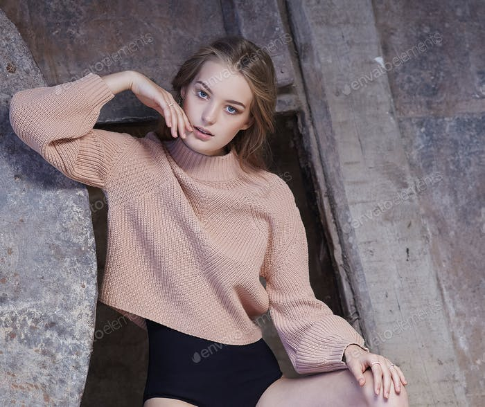 A  woman in a black panties and cream pullover.