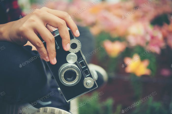 Close up woman's hand with vintage camera focus shooting flowers at garden.