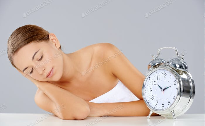 Woman sleeping alongside an alarm clock