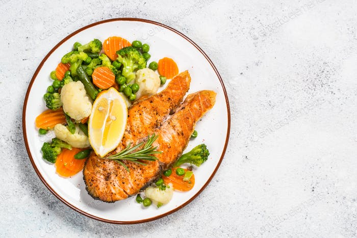 Grilled salmon fish steak with vegetables on white