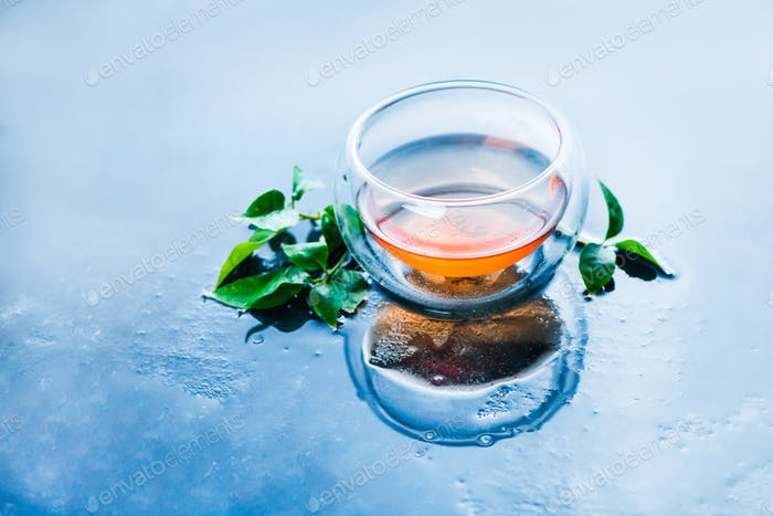 Double wall glass with tea leaves on a light blue background. Hot drink header with copy space