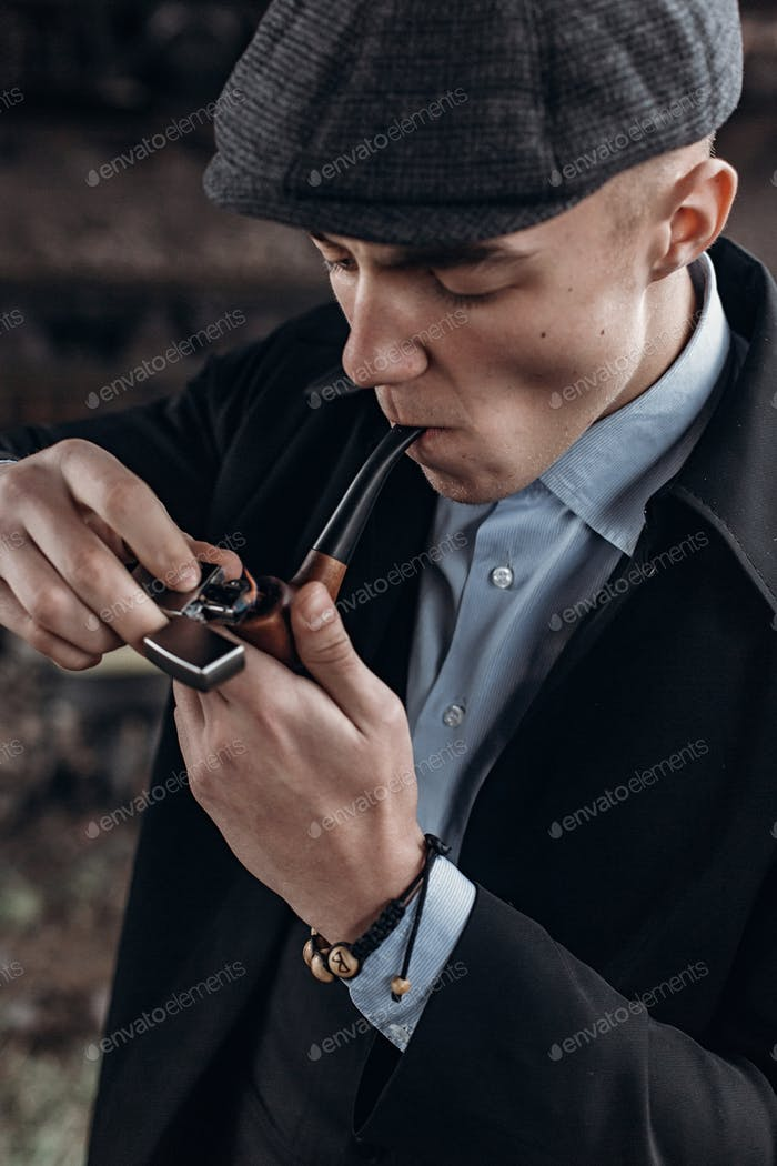 Man in retro outfit, smoking, lighting wooden pipe