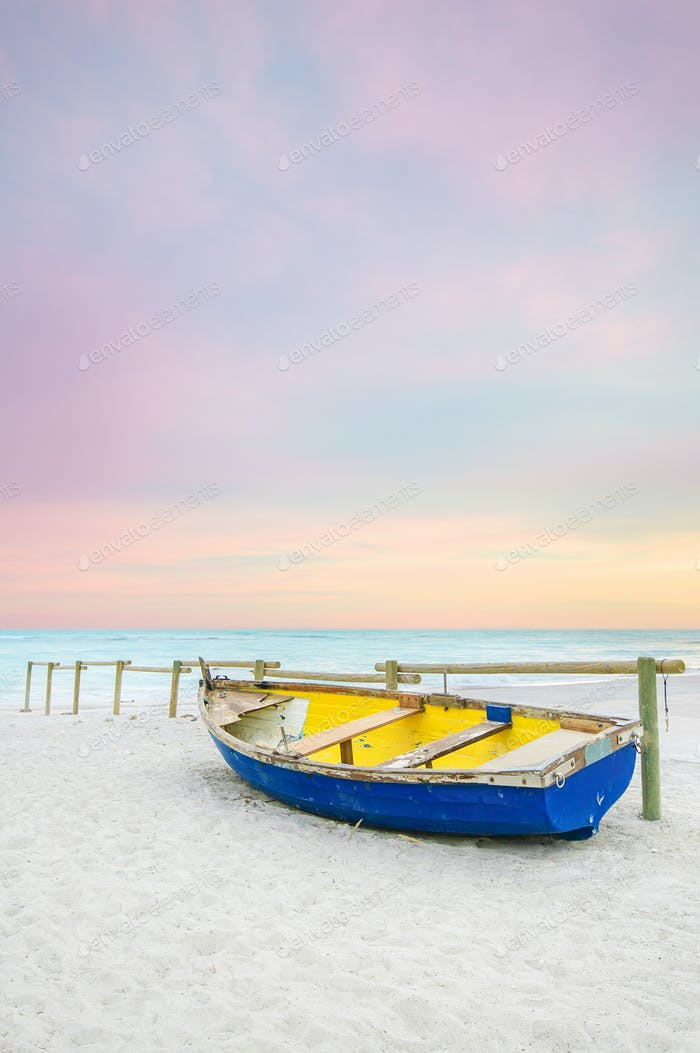 Old yellow blue wooden boat on white beach on sunset