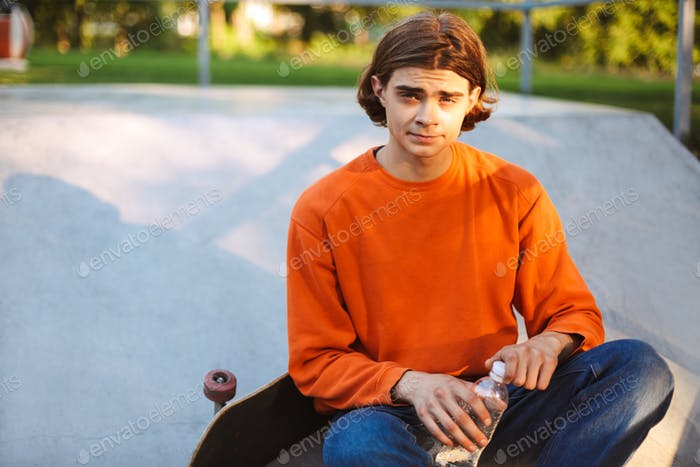Young skater in orange pullover holding bottle of water in hands
