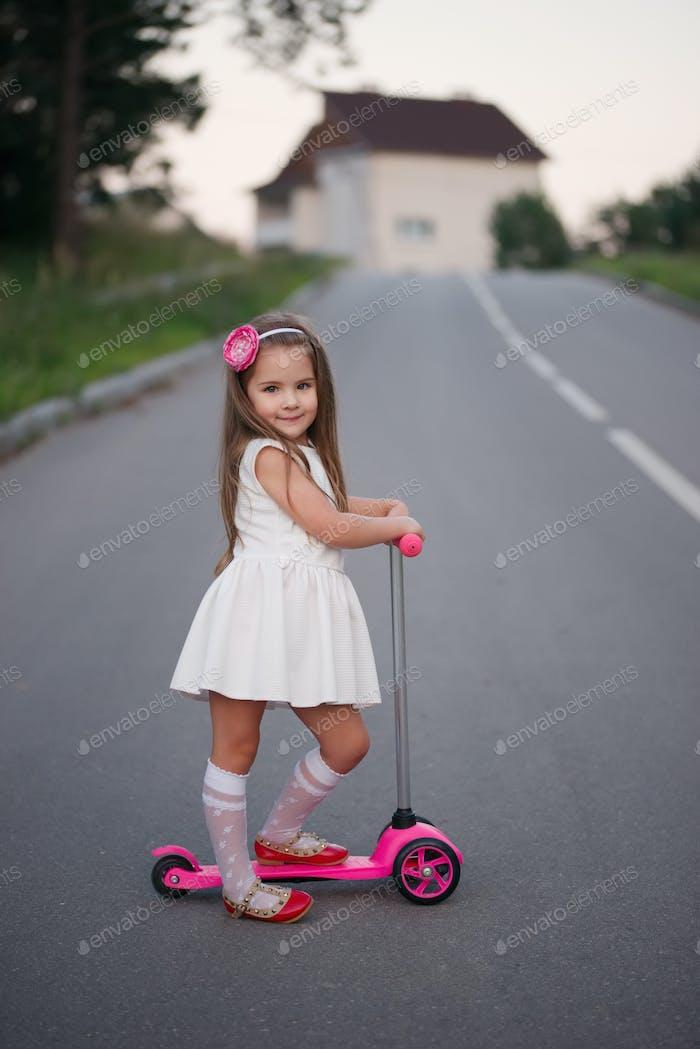 kleines Mädchen mit Roller auf der Straße