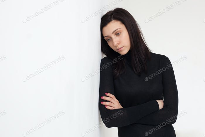 A beautiful girl in black clothes leaned her head against the white wall. She is saddened and upset