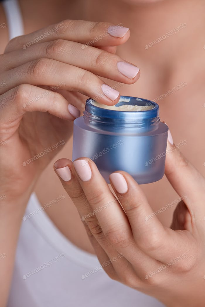 Hands of a woman  apply face cream