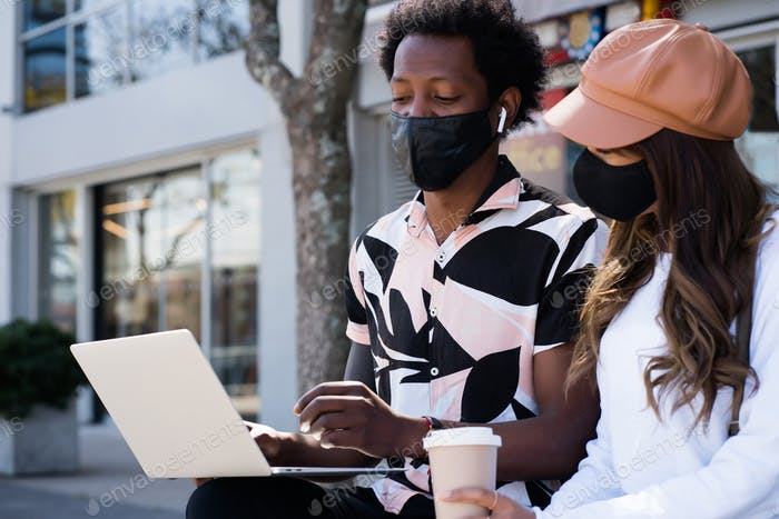 Young couple using laptop outdoors.