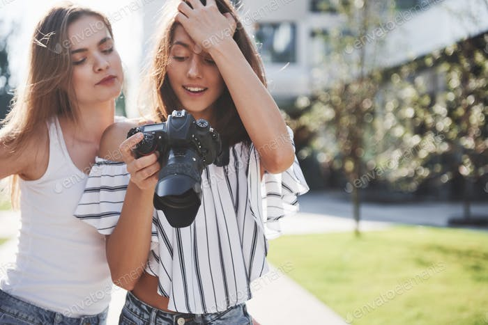 Two pretty pretty friends of the girl with the camera take photos together and walk in the city