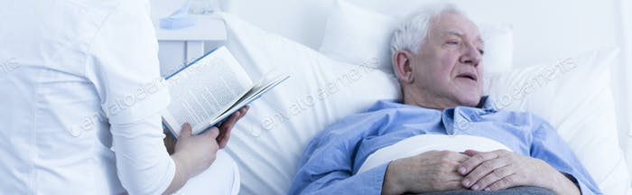 Nurse reading to elderly patient