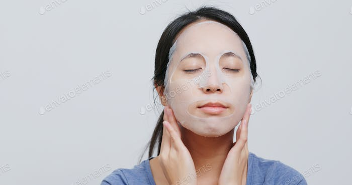 Woman apply paper face mask