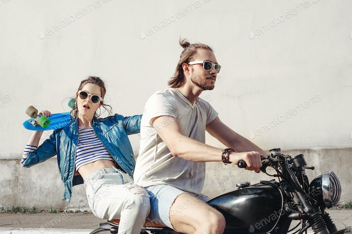Young man and woman riding on sunny day