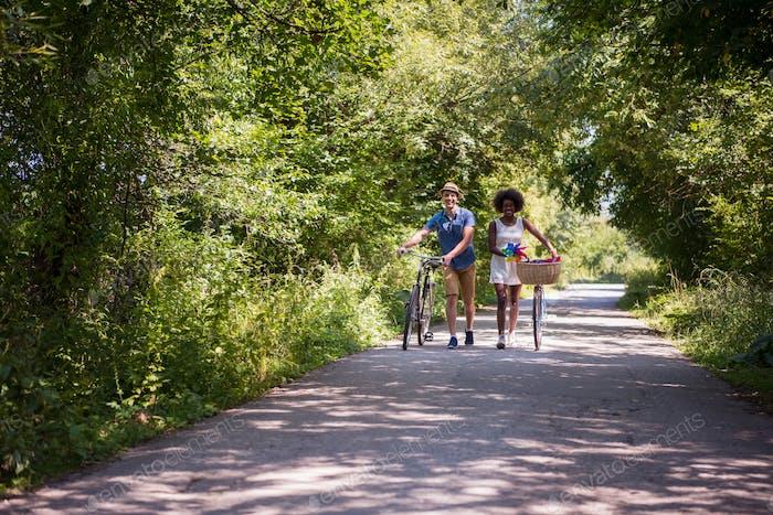 Joven pareja multiétnica tener un paseo en bicicleta en la Naturaleza