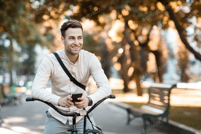 Street style. Young stylish man texting on phone while sitting on bike