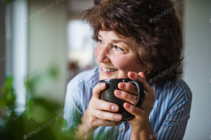 Senior woman with cup of coffee at home, relaxing