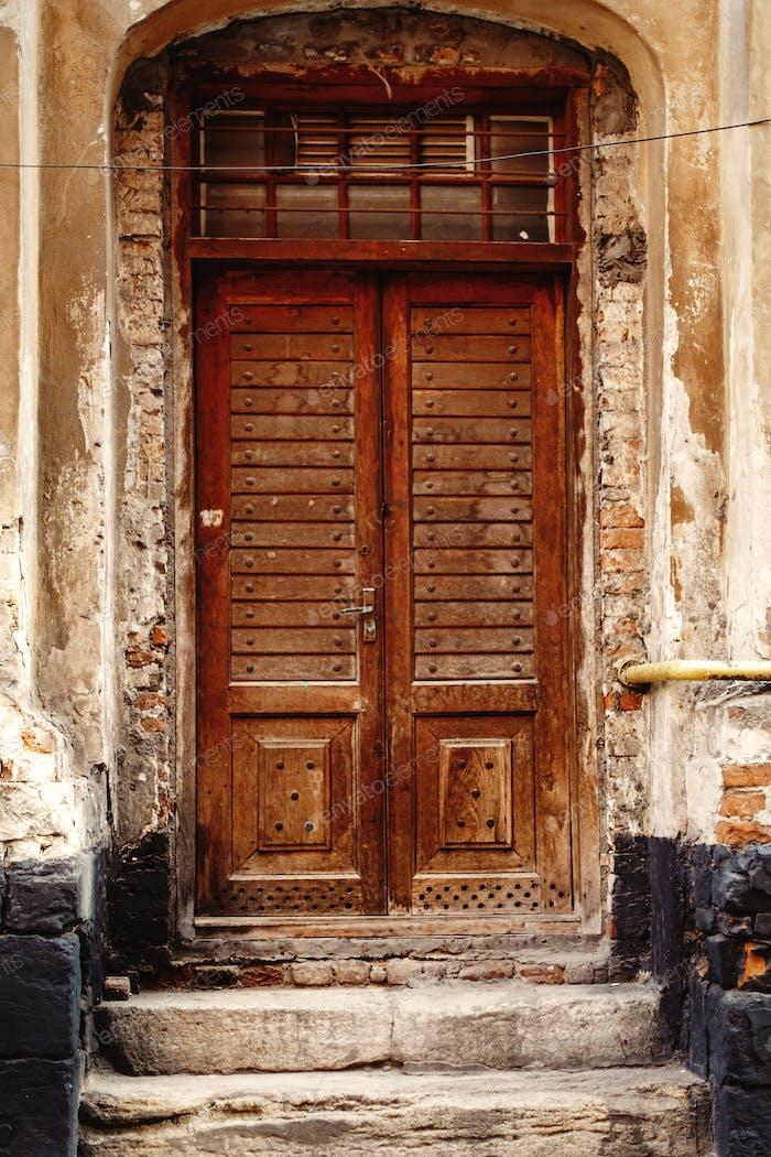 Alte Holztürfront auf Steinmauer in der europäischen Stadt