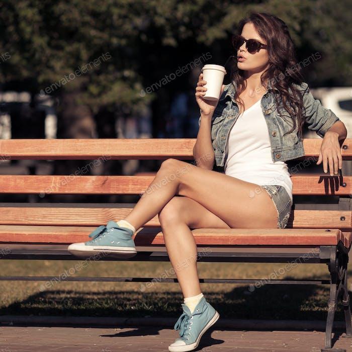 Junge Frau trinken Kaffee aus Pappbecher. Auf Bank sitzend