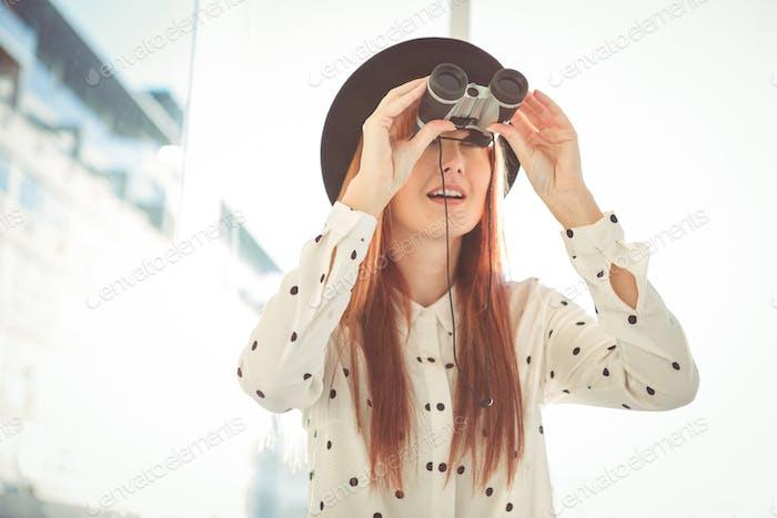 Lächelnde Hipster Frau mit Fernglas in einem hellen Raum