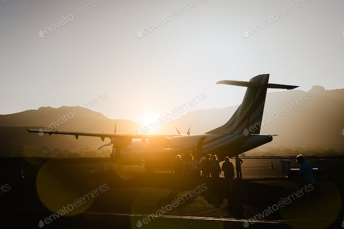 Passengers boarding to propeller aircraft on dusty morning. Mountain range surrounding runway on Sao
