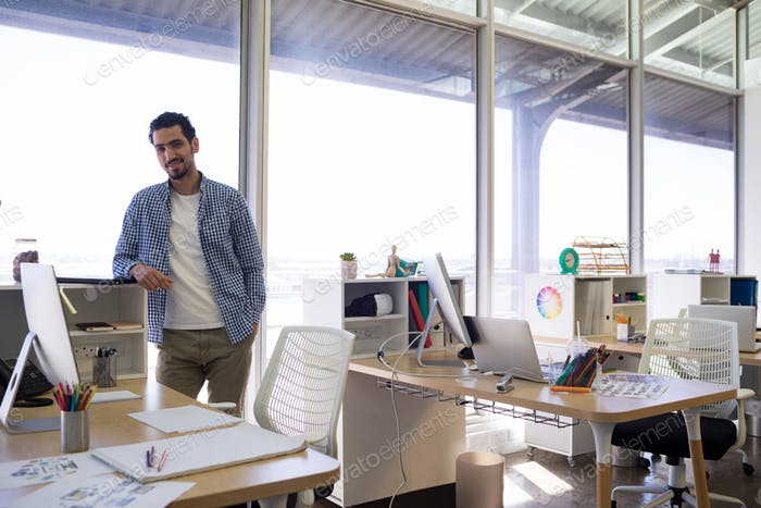 Male executive standing at his desk