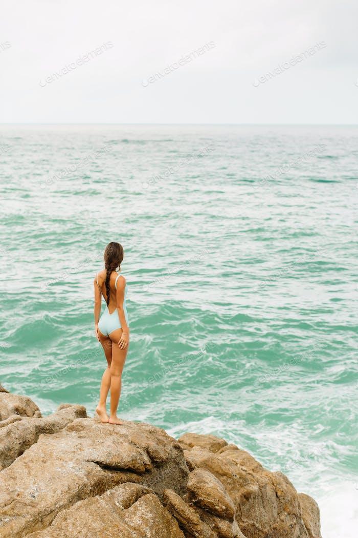 Schönes Mädchen in blauen Badeanzug zu Fuß auf großen Stein.